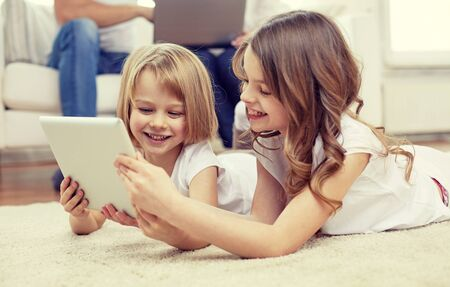 laying little: people, family, technology and children concept - happy little girls playing with tablet pc computer at home Stock Photo
