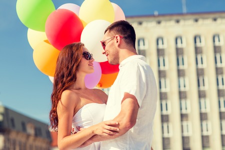 love, wedding, summer, dating and people concept - smiling couple wearing sunglasses with balloons hugging and looking to each other in city