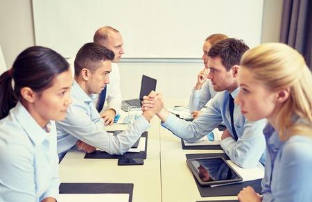 negocios, personas, crisis y confrontación concepto - sonriendo equipo de negocios sentado en lados opuestos y la lucha de brazo en el cargo