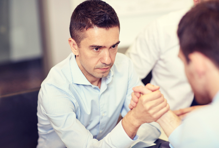 confrontation: business, people, crisis and confrontation concept - businessmen arm wrestling in office