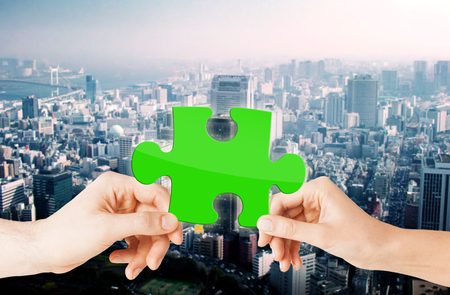 urbanization: nature, ecology, energy saving, urbanization and people concept - close up of couple hands with green puzzle over city background Stock Photo