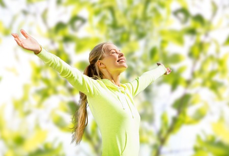 raising: fitness, sport, happiness and people concept - happy woman raising hands over green tree leaves background