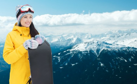 woman clothes: winter, leisure, sport and people concept - happy young woman in ski goggles with snowboard over snowy mountain background