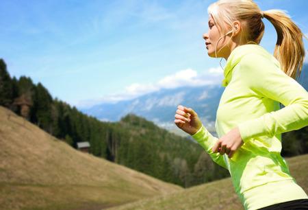 피트니스, 스포츠, 사람, 기술 및 건강한 라이프 스타일 개념 - 이어폰은 조깅이나 산과 푸른 하늘을 배경 위에 실행하는 행복 한 젊은 여자