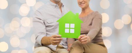 familias felices: la familia, las relaciones, los bienes raíces, la edad y el concepto de la gente - cerca de los pares mayores felices con la casa de recorte de papel verde sobre fondo de las luces Foto de archivo