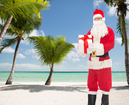 christmas costume: christmas, holidays, travel and people concept - man in costume of santa claus with gift box over tropical beach background Stock Photo