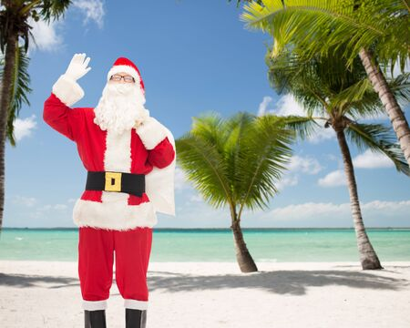 christmas costume: christmas, holidays, gesture and people concept - man in costume of santa claus with bag waving hand over tropical beach background