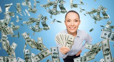 dinero: negocio, dinero, finanzas, personas y concepto de banca - la sonrisa de negocios con el montón de dinero en efectivo en dólares sobre fondo azul Foto de archivo