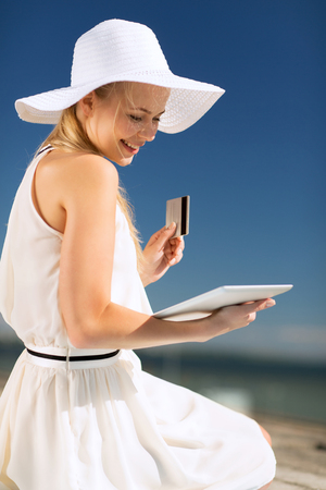 lifestyle shopping: internet and lifestyle concept - beautiful woman in hat doing online shopping outdoors Stock Photo
