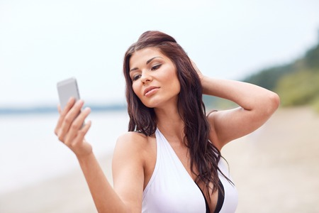 summer, travel, technology and people concept - sexy young woman taking selfie with smartphone on beach