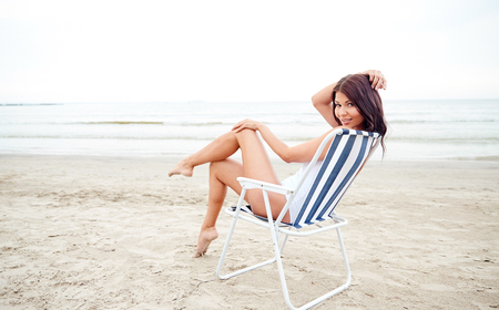 folding chair: summer vacation, tourism, travel, holidays and people concept - smiling young woman sunbathing in lounge or folding chair on beach