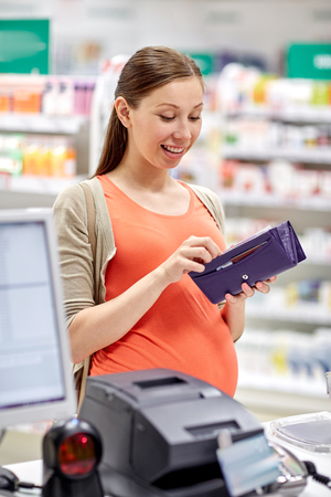 maquina registradora: la medicina, la farmacia, la atención de la salud y el concepto de la gente - mujer embarazada feliz con la carpeta en la droguería en la caja monedero Foto de archivo
