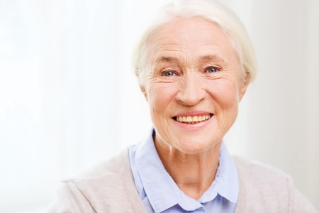 happy smiling: age and people concept - happy smiling senior woman face at home