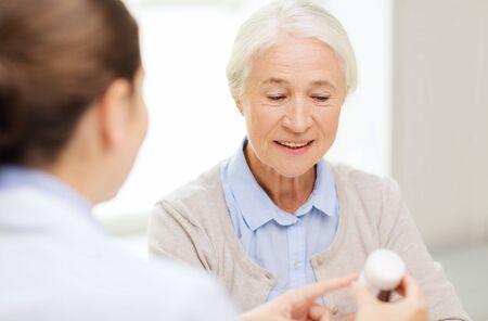 enfermera con paciente: la medicina, la edad, la salud y las personas concepto - médico mostrando píldoras a la mujer mayor feliz en el hospital