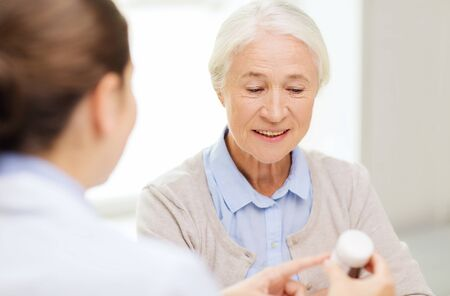 nurse practitioner: medicine, age, health care and people concept - doctor showing pills to happy senior woman at hospital Stock Photo