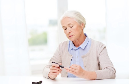 hyperglycemia: medicine, age, diabetes, health care and people concept - senior woman with glucometer checking blood sugar level at home