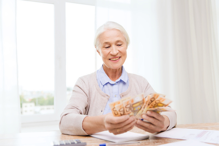 business savings: business, savings, annuity insurance, age and people concept - happy senior woman with calculator and bills counting euro money at home