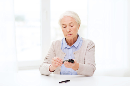home health care: medicine, age, diabetes, health care and people concept - senior woman with glucometer checking blood sugar level at home