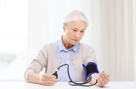 hypotension: medicine, age, health care and people concept - senior woman with tonometer checking blood pressure level at home