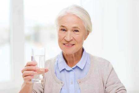vaso con agua: la edad, la salud y las personas concepto - mujer feliz altos con un vaso de agua en el hogar Foto de archivo