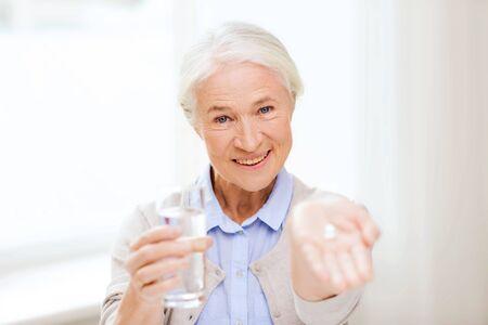 vaso con agua: la edad, la medicina, la salud y las personas concepto - mujer feliz senior con pastillas y vaso de agua en el hogar
