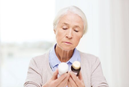 home health care: age, medicine, health care and people concept - senior woman looking at jars with medicine at home or hospital office