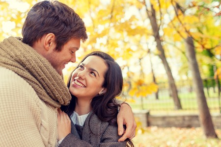 romantic love: love, relationship, family and people concept - smiling couple hugging in autumn park Stock Photo