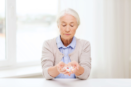 home health care: age, medicine, health care and people concept - senior woman with pills at home or hospital office