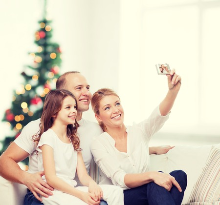xmas tree: family,  holidays, technology and people - smiling mother, father and little girl making selfie with camera over living room and christmas tree background Stock Photo