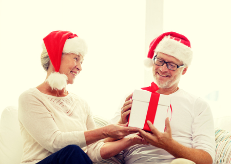 happy christmas: family, holidays, christmas, age and people concept - happy senior couple in santa helper hats with gift box at home