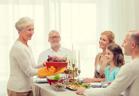 table: family, holidays, generation and people concept - smiling family having dinner at home