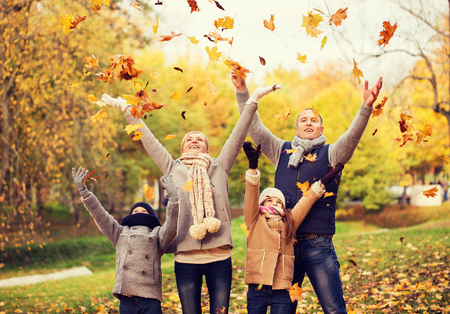 warm clothes: family, childhood, season and people concept - happy family playing with autumn leaves in park