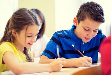 niños escribiendo: educación, escuela primaria, el aprendizaje y el concepto de personas - grupo de niños escolares con bolígrafos y cuadernos de escritura de prueba en el aula Foto de archivo