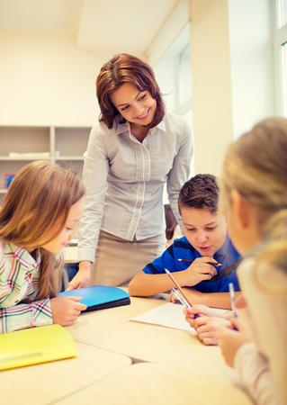 profesores: educaci�n, escuela primaria, el aprendizaje y el concepto de la gente - Profesor de ayudar a ni�os de la escuela de escritura de prueba en el aula Foto de archivo