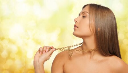 chainlet: beauty, luxury, people, holidays and jewelry concept - beautiful woman wearing golden necklace or chainlet over yellow lights background Stock Photo
