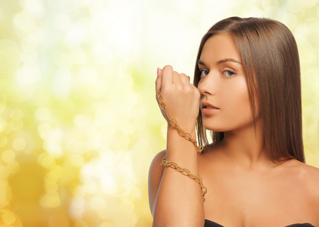 chainlet: beauty, luxury, people, holidays and jewelry concept - beautiful woman with golden chainlet over hand yellow lights background