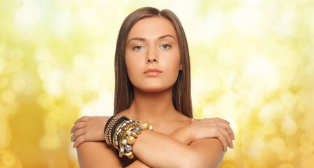 supercilious: beauty, luxury, people, holidays and jewelry concept - beautiful woman with bracelets over yellow lights background