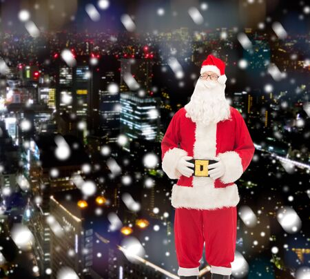 snow man party: christmas, holidays and people concept - man in costume of santa claus over snowy night city background Stock Photo