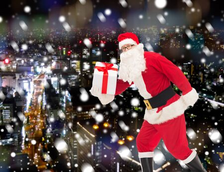 christmas costume: christmas, holidays and people concept - man in costume of santa claus running with gift box over snowy night city background