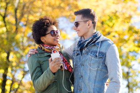 african american couple: technology, season, people and friendship concept - smiling couple with smartphone and earphones listening to music over autumn park background