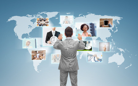 work group: business, people, communication, technology and connection concept - businessman working with world map and images on virtual screen over blue background from back Stock Photo