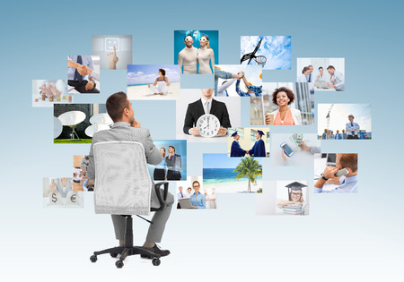 choosing: business, people, design and choice concept - businessman sitting in office chair and looking at different images over blue background from back