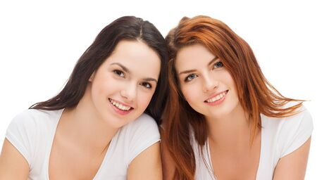 girl lying: friendship and happy people concept - two laughing girls in white t-shirt Stock Photo