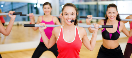 fitness trainer: fitness, sport, training, gym and lifestyle concept - smiling trainer in front of the group of people working out with barbells in the gym