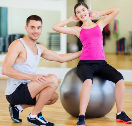 crunches: fitness, sport, training, gym and lifestyle concept - male trainer with woman doing crunches on the ball Stock Photo