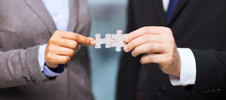 business partnership: business and office concept - businessman and businesswoman holding puzzle pieces in office