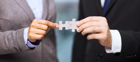 Geschäfts- und Bürokonzept - Geschäftsmann und Geschäftsfrau, Puzzleteile in Büro Lizenzfreie Bilder