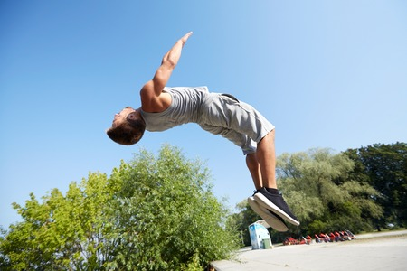 young gymnast: fitness, sport, parkour and people concept - young man jumping in summer park Stock Photo