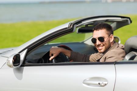 Auto bedrijf, vervoer, vrije tijd en mensen concept - gelukkig man rijden cabriolet auto buitenshuis