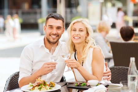 love, dating, people and holidays concept - smiling couple clinking glasses and looking to each other at restaurant lounge or terrace Stock Photo
